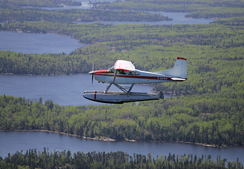 River Air float plane in flight over the English River.