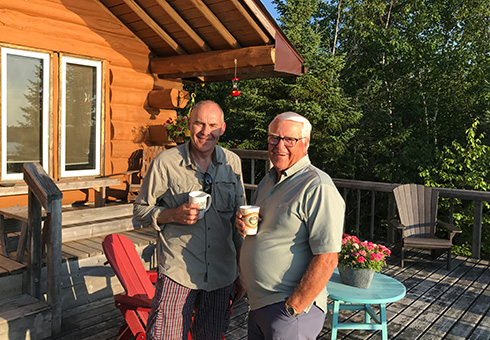 Two men enjoying coffee on the deck.