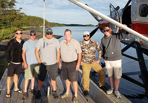 Group of six men about to board the float plane in Minaki.