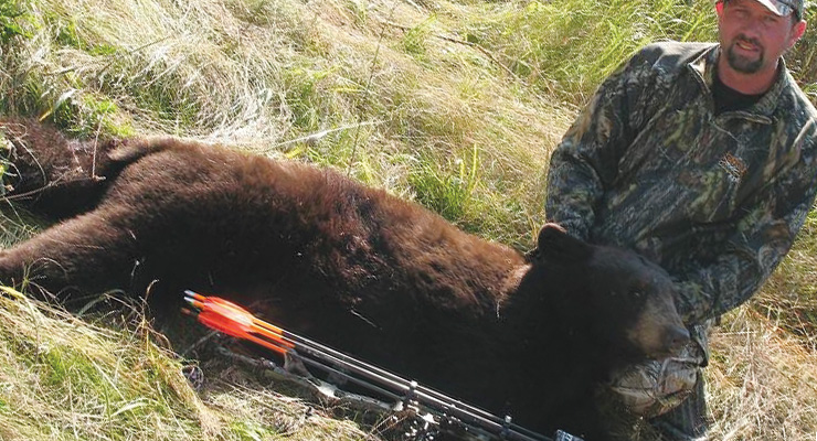 Downed black bear and the hunter.