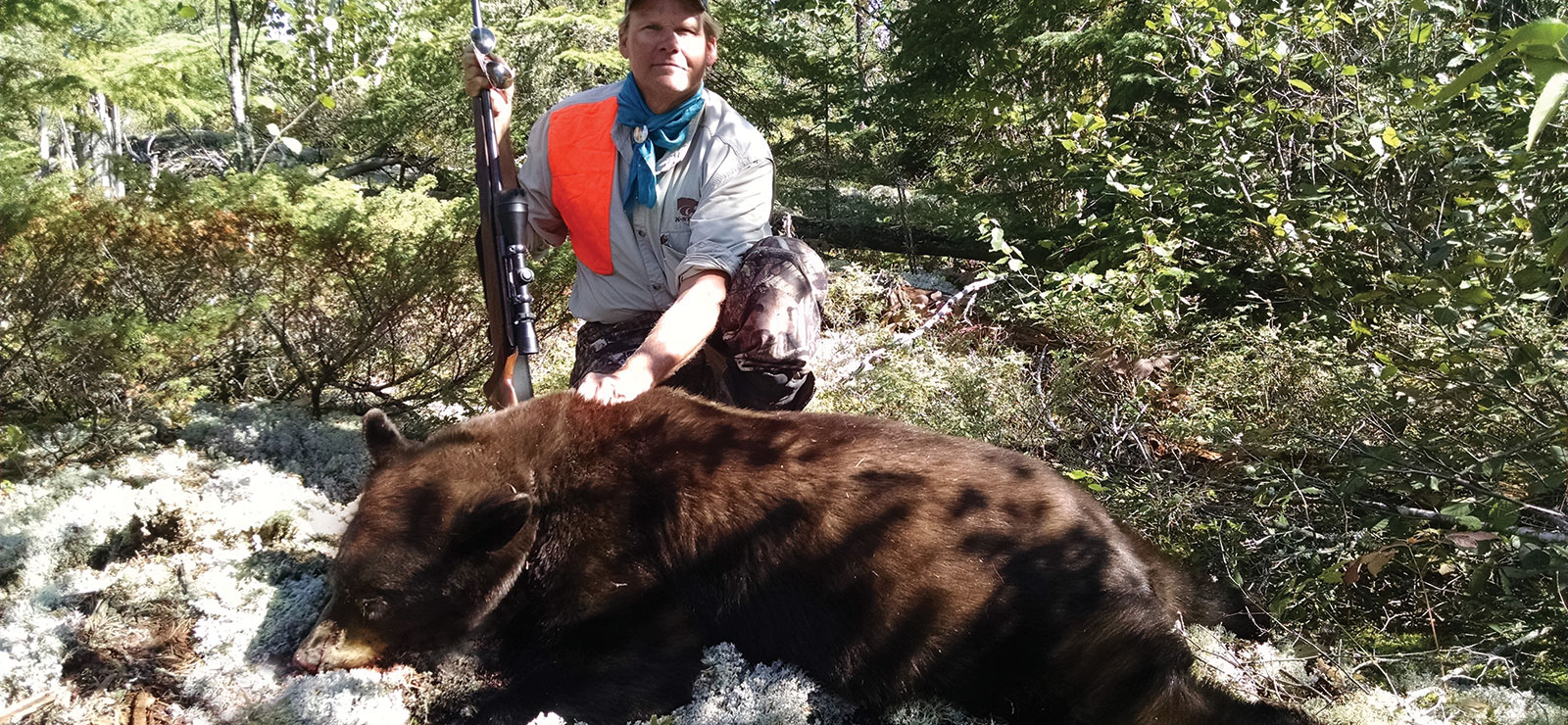 Man and rifle with downed black bear.